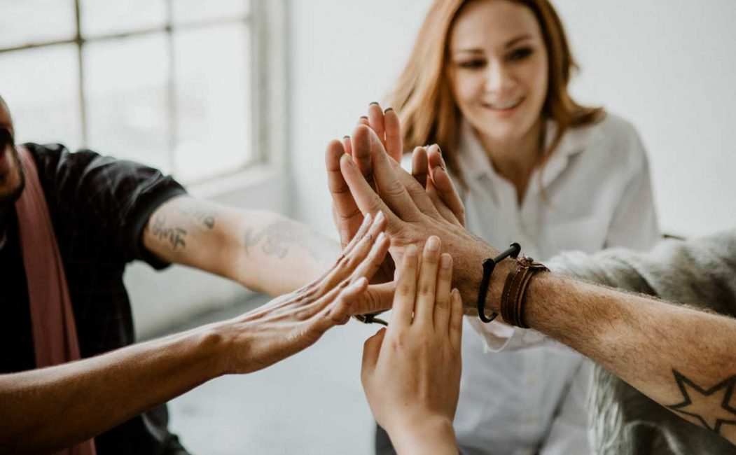 zero trust -Group of diverse team joining hand in the middle